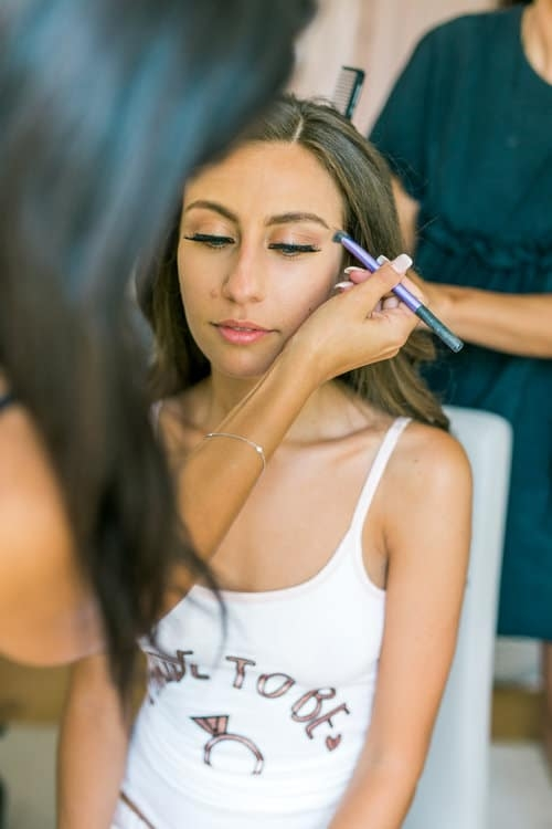 makeup artist applying makeup to bride on wedding day