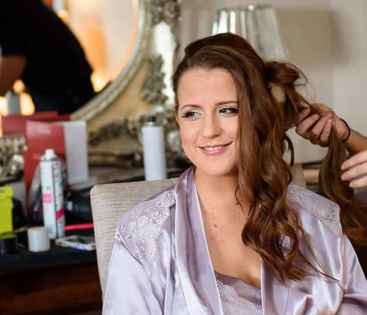 bridal hair and makeup artist Becky styling bride's hair on wedding day