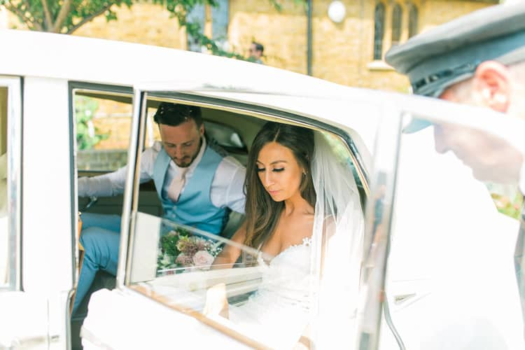 bride and groom getting out of wedding car