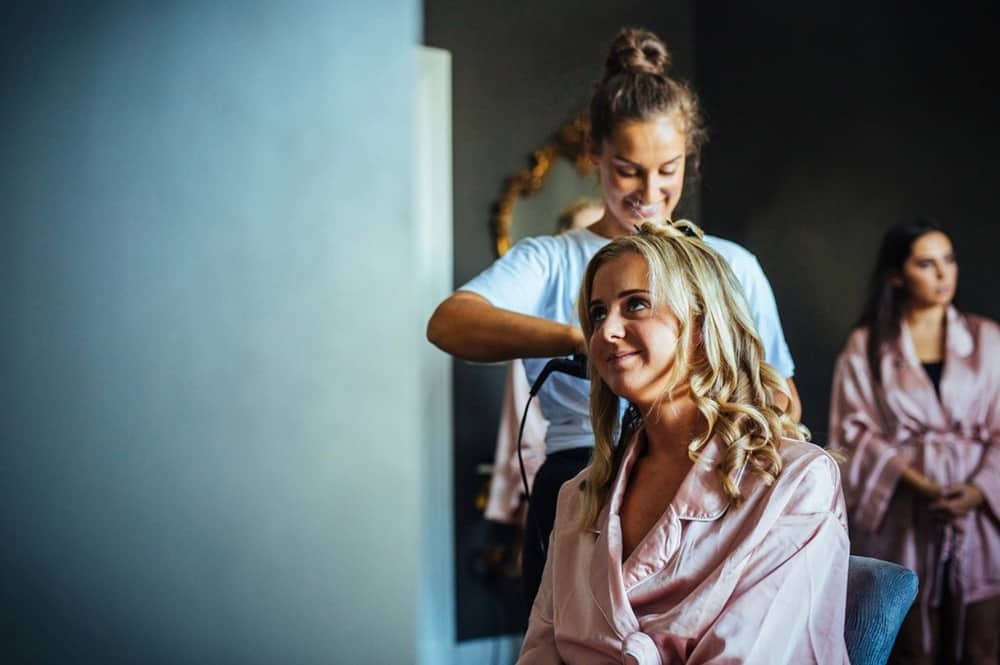 wedding hair and makeup artist chloe styling bridesmaid's hair