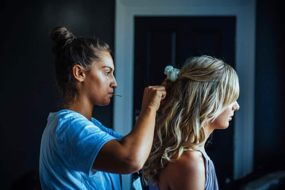 wedding hair and makeup artist chloe attaching hair accessory to bridesmaid's hair