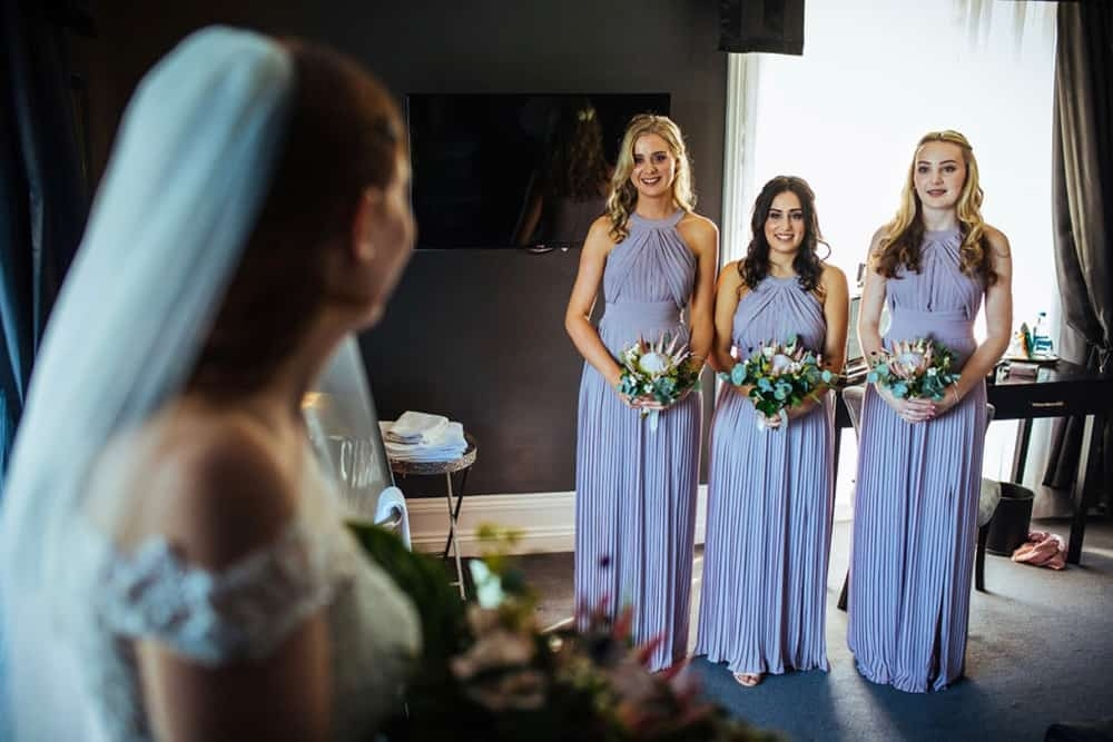 wedding photograph of three bridesmaids with bouquets looking at bride