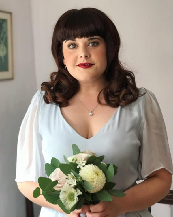 vintage bride with red lip and fringe holding bouquet