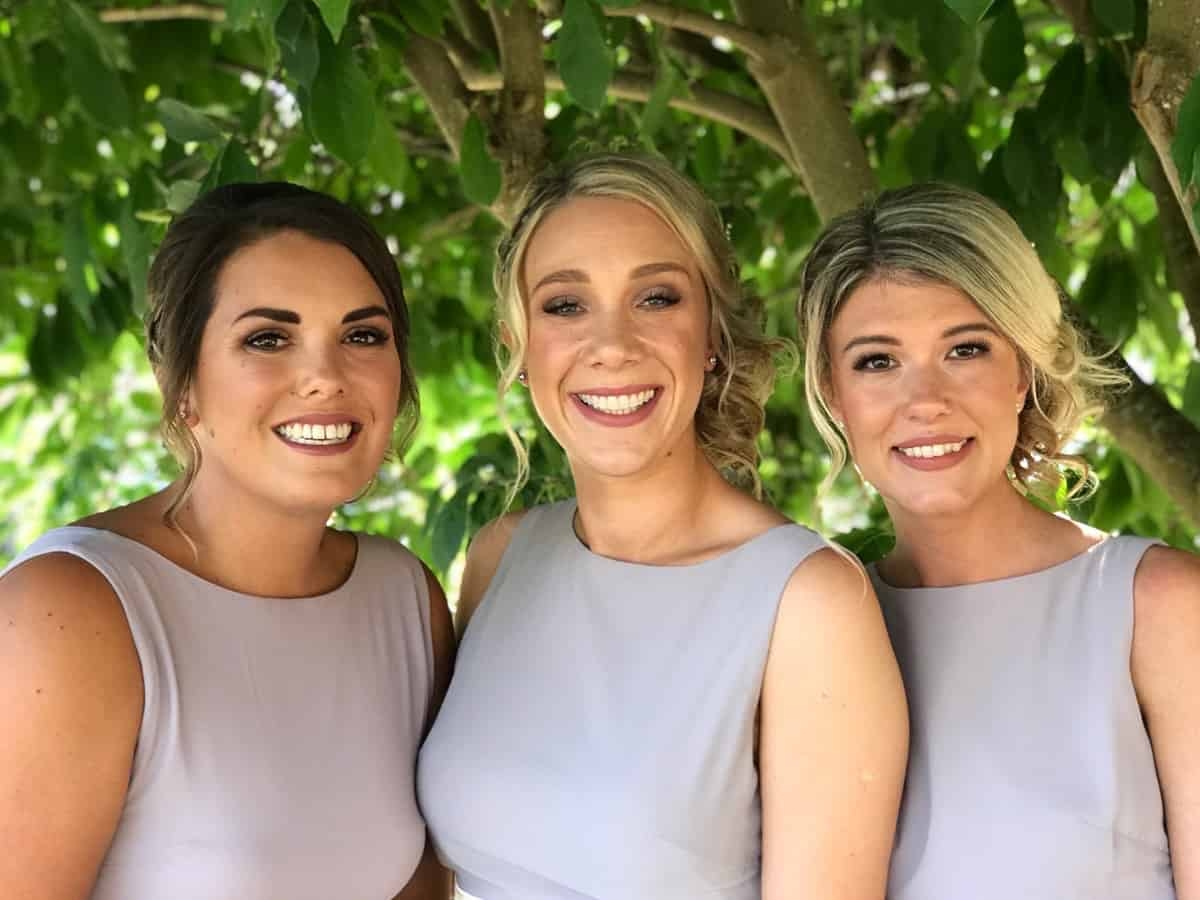beautiful happy bridesmaids posing by tree