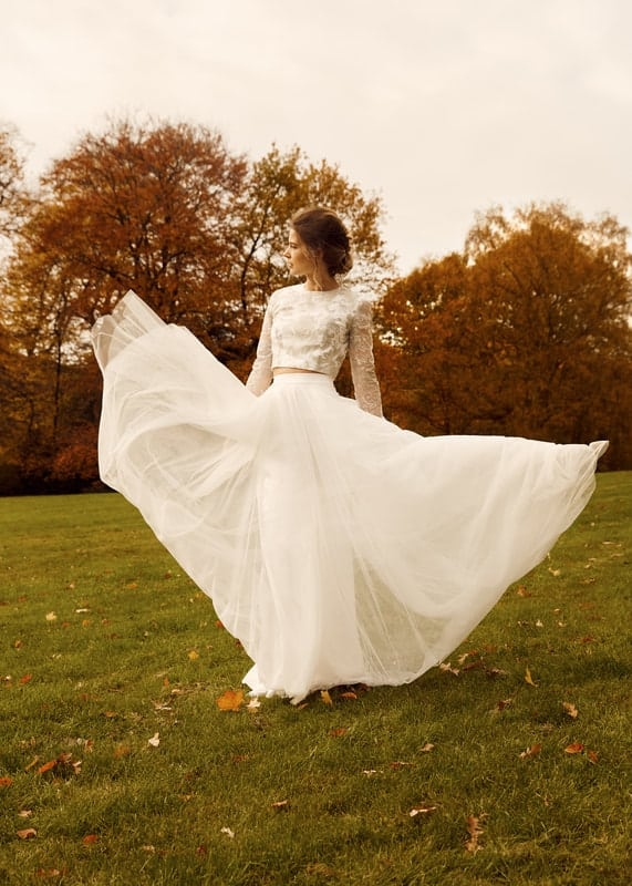 bride in field dancing with wedding dress