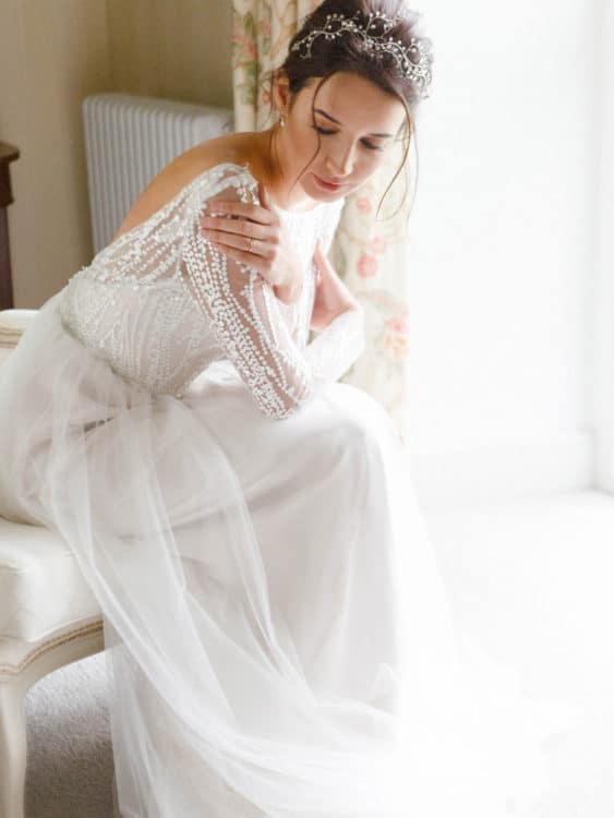 bride sitting on bed in hotel room