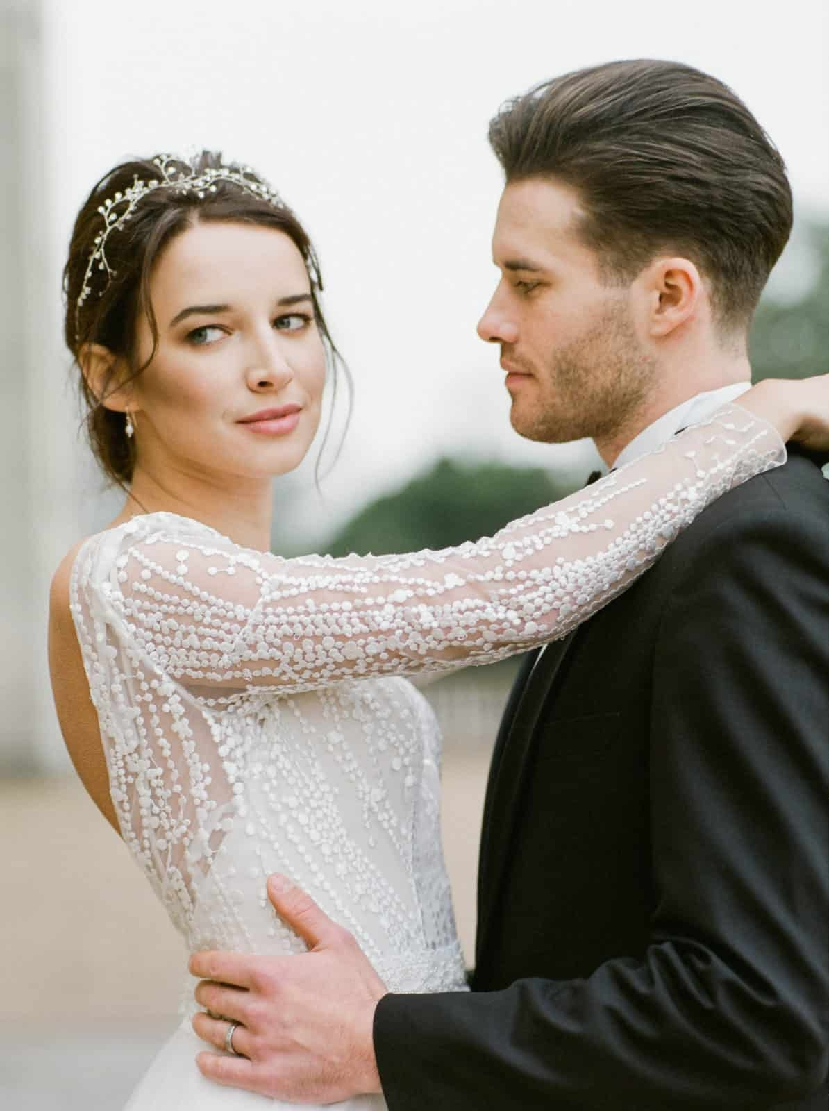 portrait of bride with long sleeved dress and groom