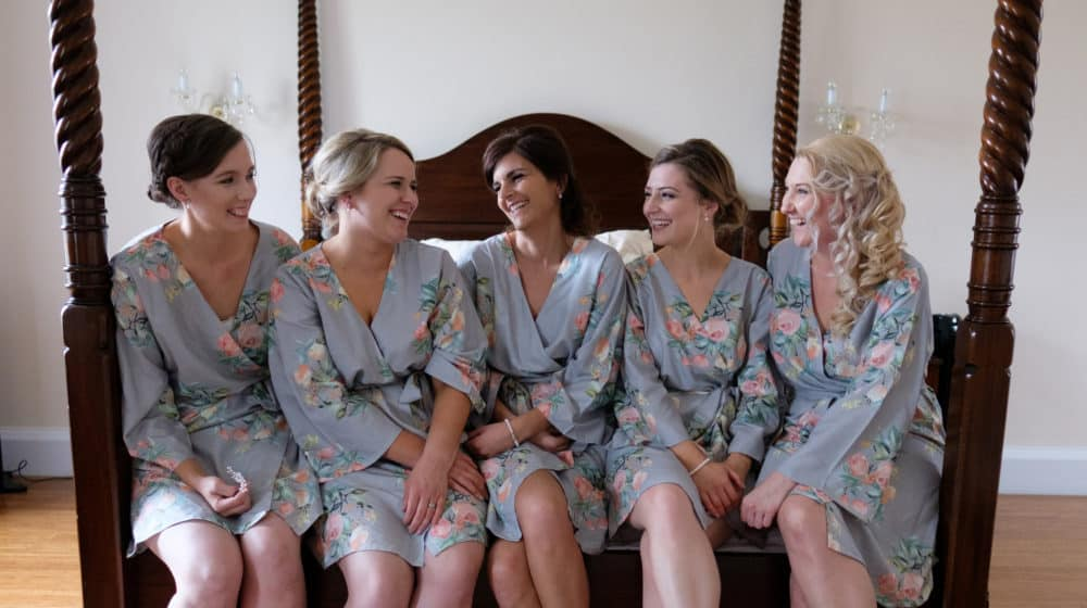 bridal party in matching dressing gowns sitting on bed