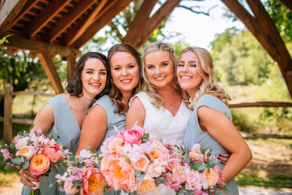 bride and bridesmaids posing with bouquets outside