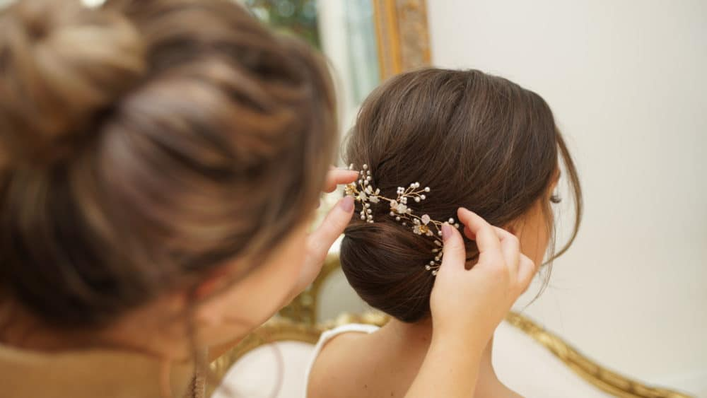 hairstylist placing in bride's hair accessory
