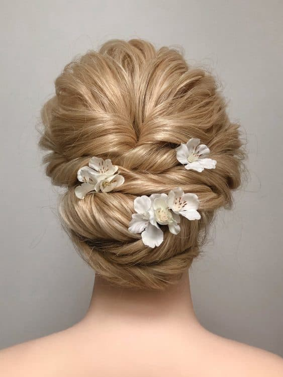 bridal updo with small white flower accessories