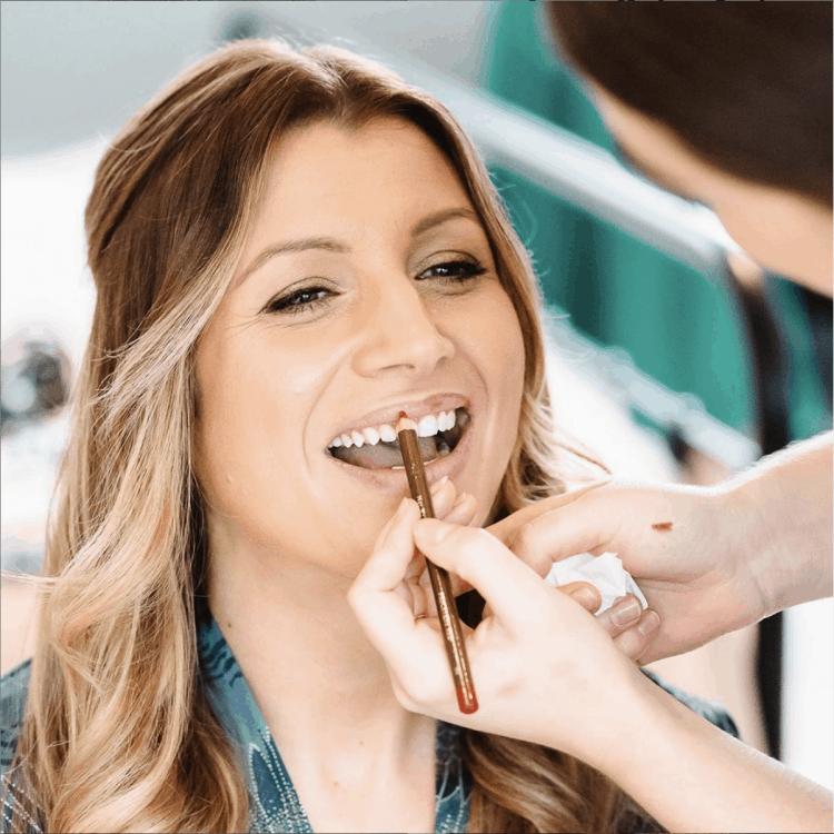 makeup artist applying lipliner to bride